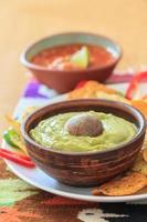 natura morta con nachos, guacamole fatto in casa, peperoncino e salsa foto