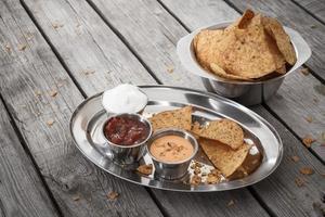 nachos con salsa di pomodoro e panna acida foto