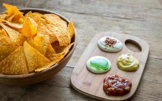 nachos al formaggio con diversi tipi di salsa foto