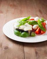 pesce al forno con mozzarella e insalata su un piatto bianco foto