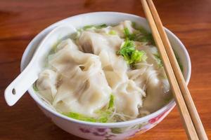 Wonton cinese e minestra di pasta saporiti. foto