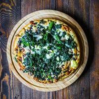 Pizza di spinaci e formaggio di capra su fondo di legno foto