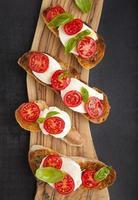 Bruschetta italiana con pomodorini, mozzarella e basi fresche foto