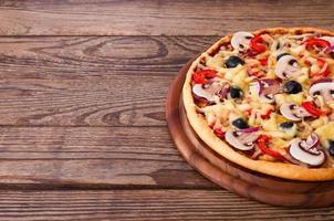 Pizza con frutti di mare sul tavolo di legno foto