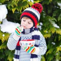 piccolo bambino divertente che tiene grande tazza con cioccolata calda
