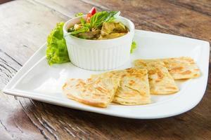 zuppa di pollo al curry rosso servita con roti.