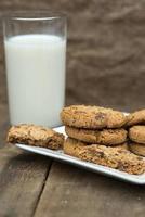 ambiente rustico con biscotti al cioccolato e bicchiere di latte foto