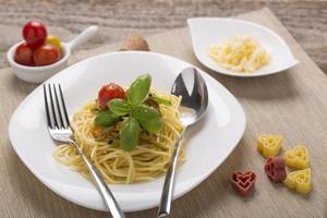 spahetti con verdure pomodori sul piatto foto