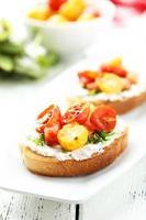 Bruschetta fresca saporita con i pomodori sul piatto foto