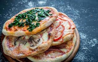 mini pizze con vari condimenti sulla tavola di legno foto
