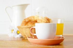 tipica colazione rurale - caffè, succo di frutta e cornetto. foto
