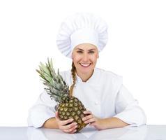 donna chef in uniforme. isolato su sfondo bianco con ananas foto