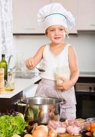 bambina che cucina con la carne foto