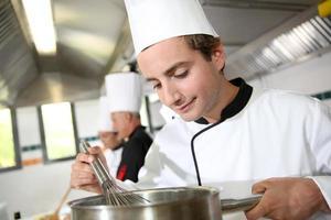giovane cuoco che lavora in cucina foto