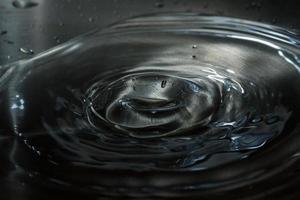gocce d'acqua che cade sulla retroilluminazione dell'acqua foto