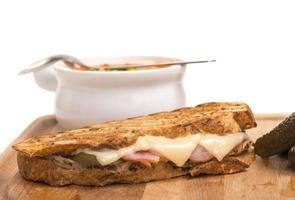 delizioso panino con prosciutto, maiale e formaggio svizzero con zuppa di verdure foto