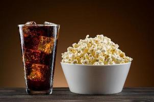 popcorn e coca cola sul tavolo foto
