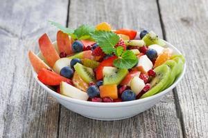 Insalata di frutta e bacche sul tavolo di legno foto