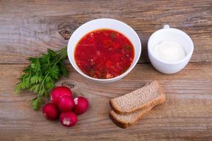 ciotola bianca di zuppa di borsch con prezzemolo e pane foto