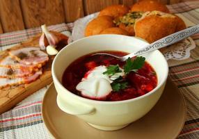 piatto di borscht caldo con panna acida, pane e carne. foto