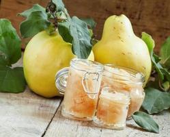 marmellata di mele cotogne rosa in vasetti di vetro e mela cotogna fresca