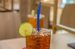 tè freddo al limone / bevanda ghiacciata con fettine di lime e ghiaccio.