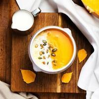 zuppa di zucca con panna montata e semi in un bianco foto