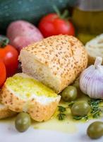 olio extra vergine di oliva su baguette e verdure bianche foto