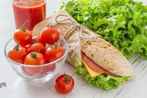 panino estivo con prosciutto, formaggio, insalata e pomodori, succo di frutta foto