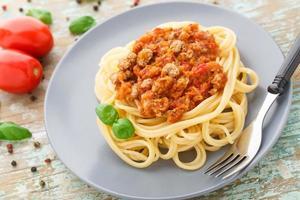 spaghetti alla bolognese con foglie di basilico