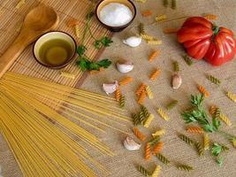spaghetti secchi crudi su una superficie rustica con pomodoro, aglio, foto