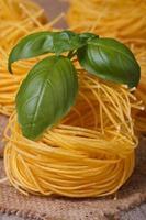 primo piano del nido di pasta secca con basilico verde sul tavolo.