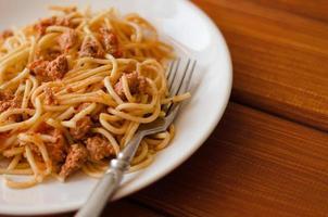 spaghetti con salsa su un piatto bianco