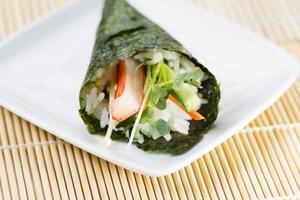 singolo cono di sushi sul piatto bianco foto