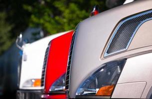 frammento della parte anteriore di camion semi in piedi in fila foto
