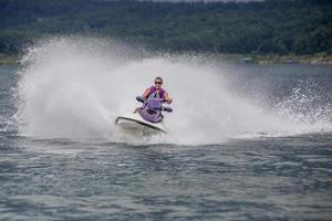 giovane donna che guida un jet ski foto