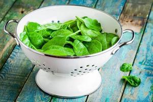 spinaci freschi crudi in uno scolapasta bianco foto