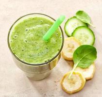 bicchiere di banana, spinaci e frullato di cetriolo con una cannuccia foto