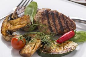 grigliare la carne, con verdure fresche sul piatto ricamato foto
