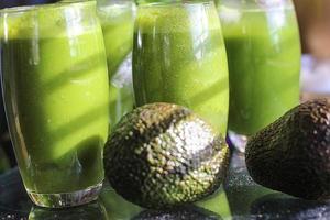 avocado e bicchieri di frullati verdi foto