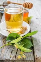 Tè alle erbe in tazza di vetro, miele, fondo di legno rustico foto