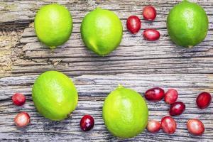 agrumi lime con mirtilli rossi su assi di legno foto