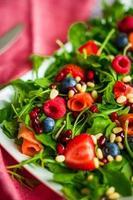 insalata sana con rucola, spinaci, salmone affumicato e frutti di bosco foto