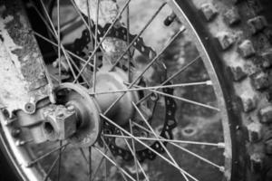 vicino frammento monocromatico della ruota di moto motocross sport anteriore foto