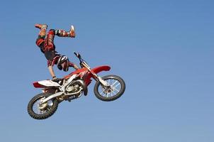 corridore di motocross eseguendo di nuovo acrobazia con la moto a mezz'aria foto