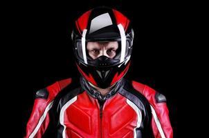 motociclista nel casco su sfondo nero foto