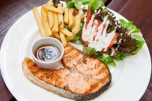 trancio di salmone con insalata e patatine fritte.