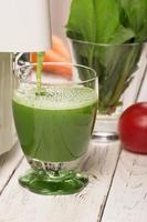 succo di spinaci da spremiagrumi versando in un bicchiere foto