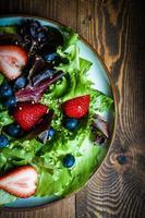 insalata verde con frutti di bosco su fondo in legno