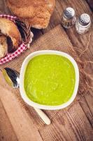 zuppa di piselli in ciotola con pane e panna acida foto